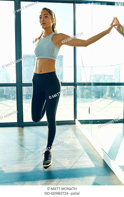 Young woman exercising in gym, stretching