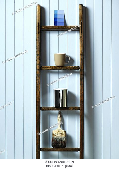 Ladder against wall with painting supplies on rungs