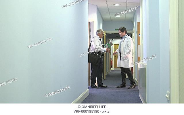 Two male doctors shaking hands in corridor