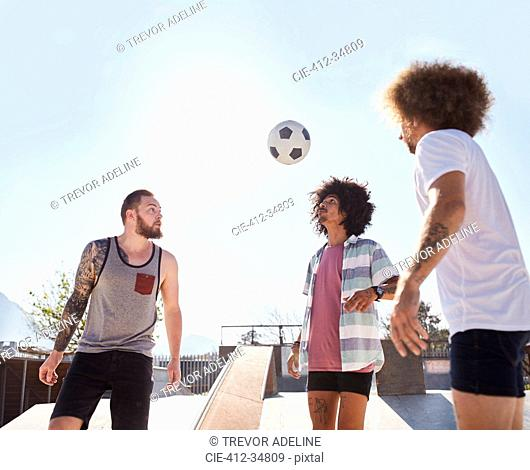 Male friends playing soccer at sunny skate park