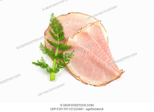 slices of ham and twig of fresh dill on white background