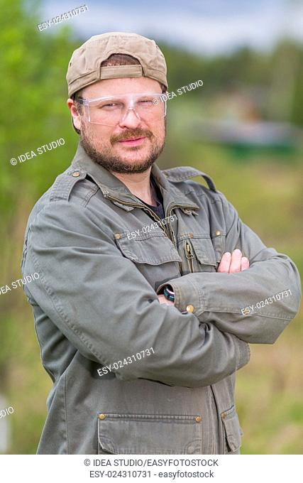 Solid worker in safety glasses on natural background