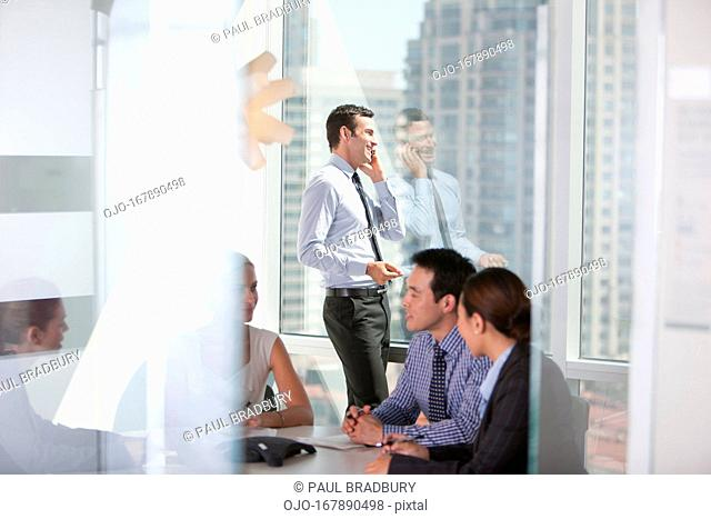 Businessman talking on cell phone in meeting