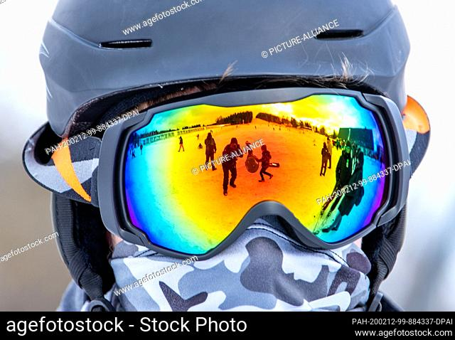 dpatop - 12 February 2020, Saxony, Altenberg: The ski slope is reflected in the ski goggles of a snowboarder. A thin layer of snow attracts holidaymakers to the...