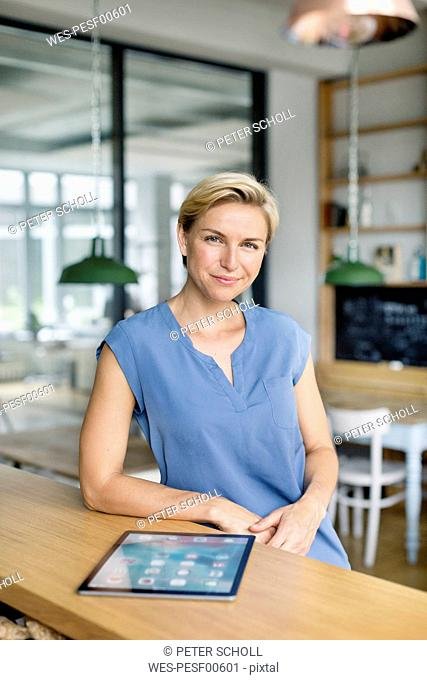 Portrait of confident blond woman with tablet