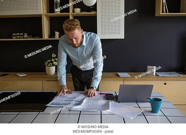 Man with laptop studying plans on table at home