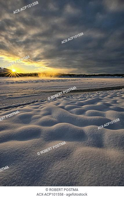 The sun creates a sunburst as is crests a hill along the Stewart River in the town of Mayo, Yukon, Canada. Snow blankets the rocky shoreline
