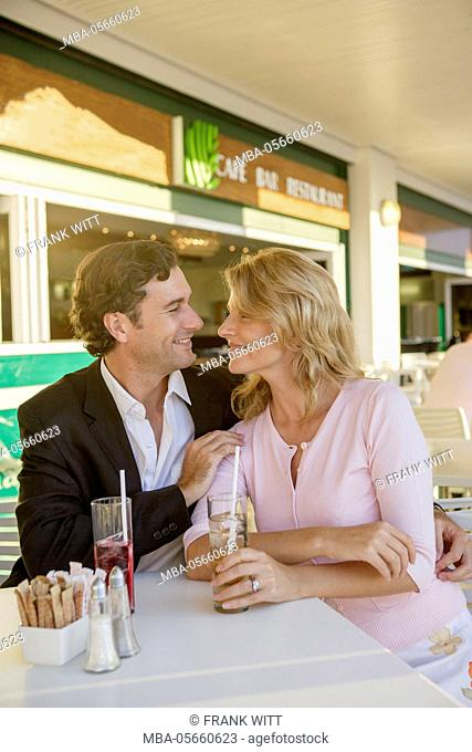 Couple is sitting arm in arm with drinks on cafe terrace in summery clothes