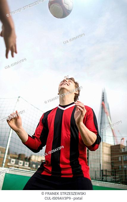 Young man practising football skills on urban football pitch