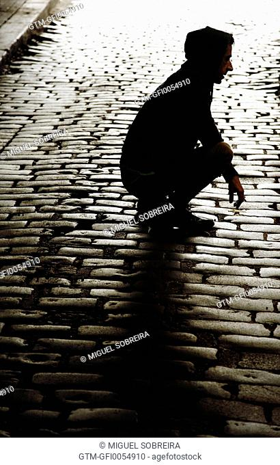 Man Crouched on Cobbled Alleyway
