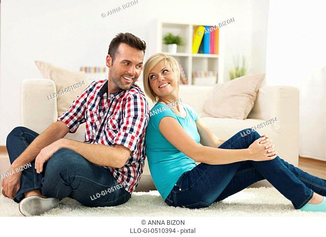 Loving couple sitting on carpet at home. Debica, Poland