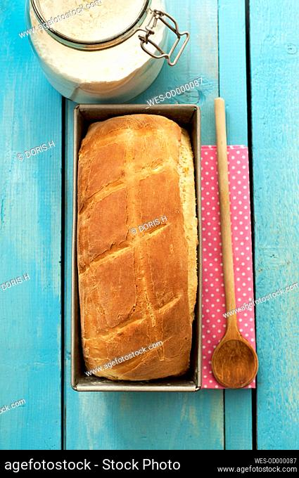 White bread in baking tray with wooden spoon and napkin