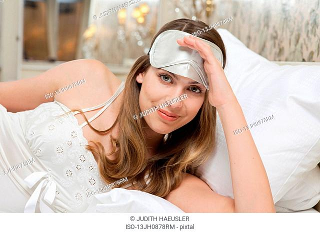 woman, sleeping mask on head, laughing