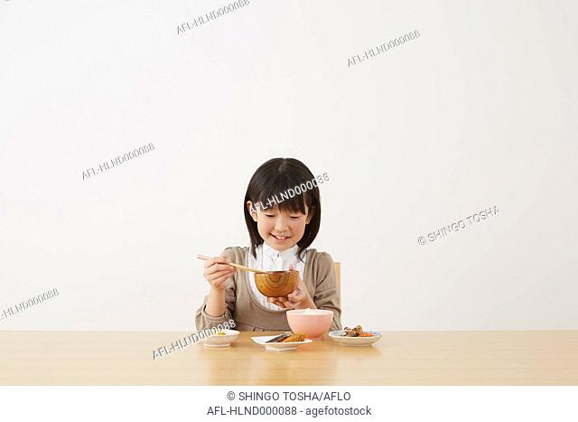 Young girl eating on wooden table