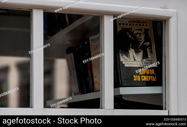A picture of a group of books sitting on a shelf inside a phone booth