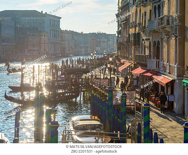 Grand canal with sun reflection and gondola and walkway in Rialto. Venice, Italy