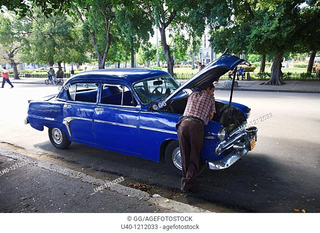 Cuba, Havana, man fixing car