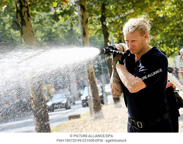 20 July 2018, Germany, Duesseldorf: A firefighter watering banana trees in downtown Duesseldorf. The distressed trees are in urgent need of water after weeks of...
