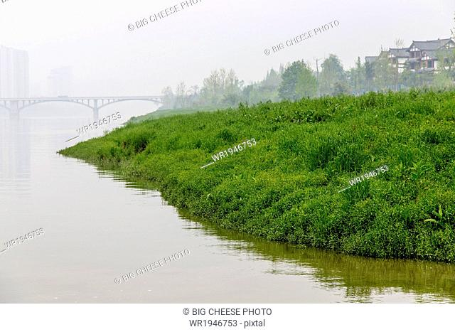 Misty bridge and a riverside village, Leshan, Sichuan province, China