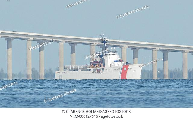ST. PETERSBURG, FL - APRIL 22: USCGC Venturous moves through Tampa Bay, with the Sunshine Skyway Bridge in the background on April 22, 2015 in St