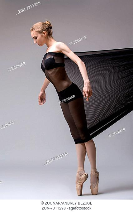 Slim dancer plays with black mesh fabric in the studio on a white background in lingerie