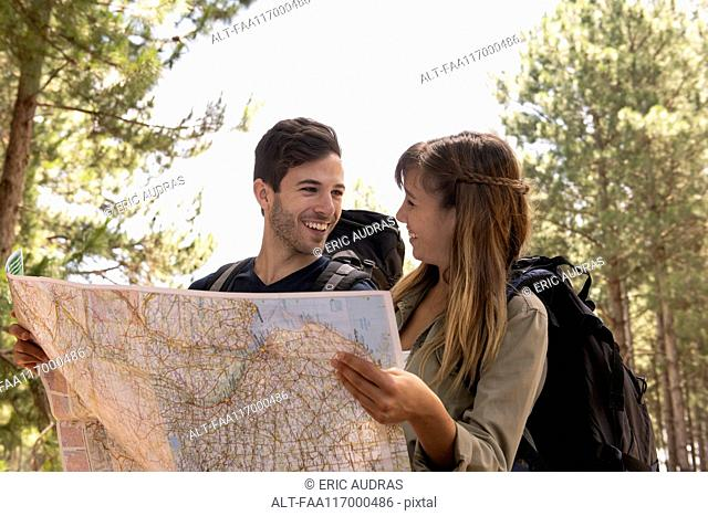 Young couple standing with map in pine forest