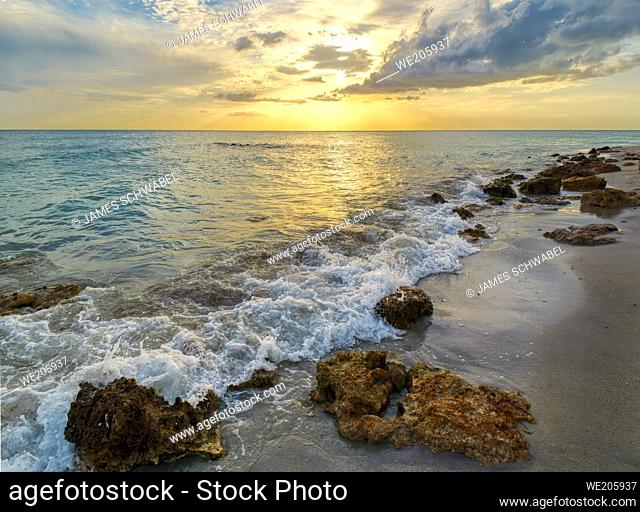 Rocky shoreline of Caspersen Beach in Venice Florida USA with a yellow orange sunset over the Gulf of Mexico