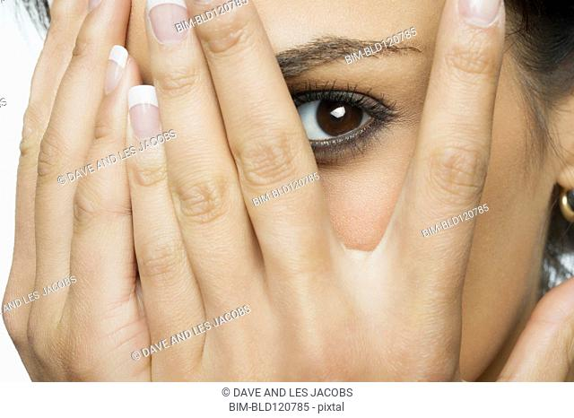 Middle Eastern woman peeking out from between fingers