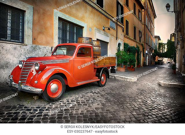Red retro car on the street of Trastevere in Rome, Italy