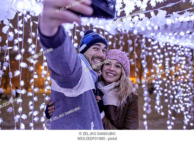 Happy young couple in winter decoration taking a selfie