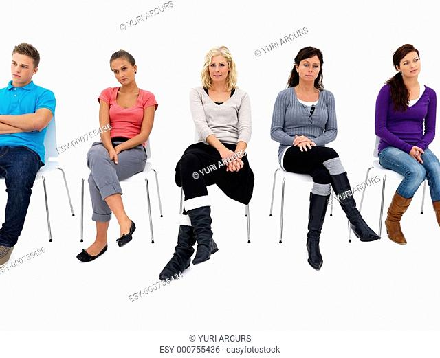 Full length portrait of a man and women sitting on chair against white background