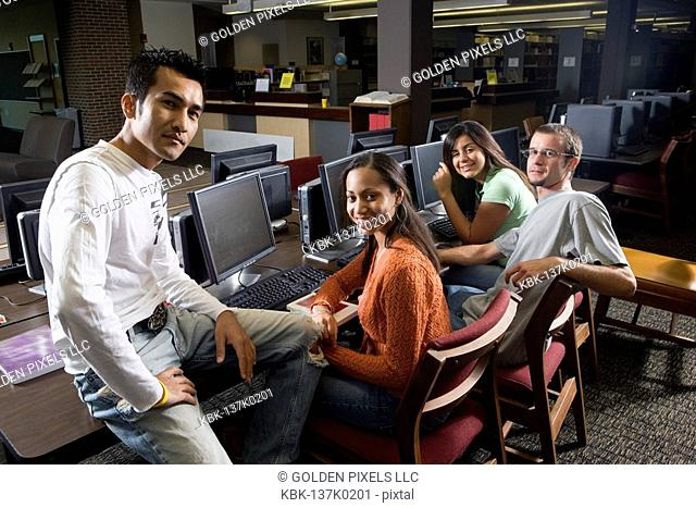 Portrait of students sitting together while using computers in the library