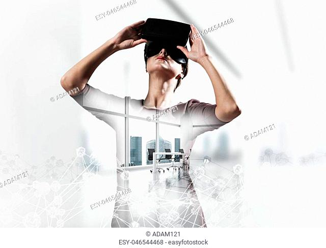 Young and beautiful woman in red dress using virtual reality headset with digital network structure while standing inside office