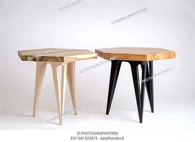 Two modern wooden coffee tables with hexagonal tops, one with painted black legs