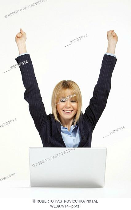 Happy blonde business woman working in office with laptop raising hands for victory