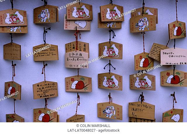 Ema are small wooden plaques on which Shinto worshipers write their prayers or wishes. The ema are then left hanging up at the shrine