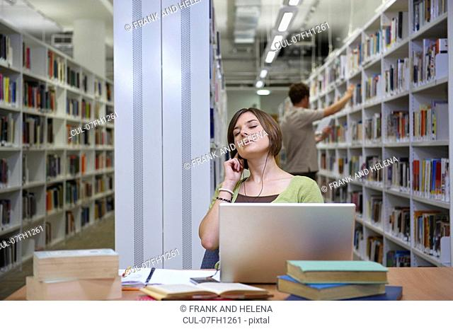 Young woman seated in library
