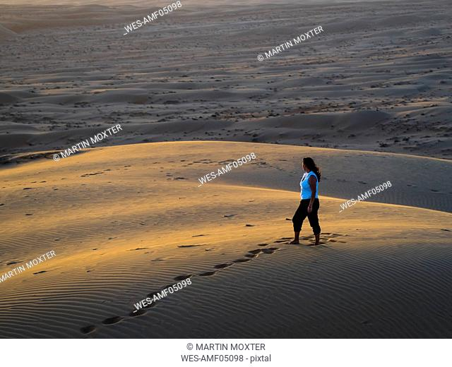 Oman, Al Raka, young woman standing on a desert dune in Rimal Al Wahiba desert watching sunset