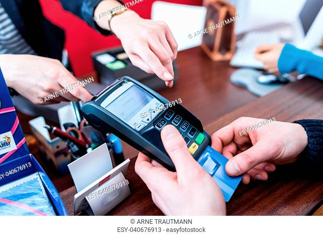 Customer paying with credit card in modern shop