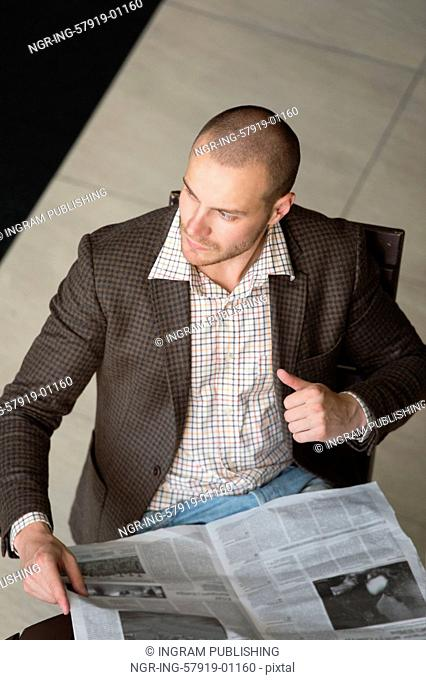 Handsome businessman or manager in office building reading newspaper view from above