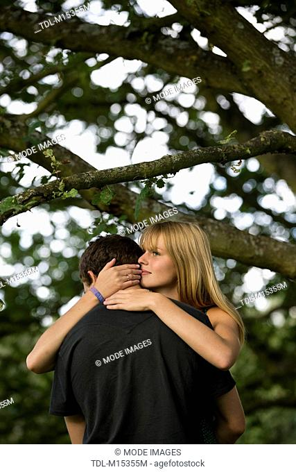 A young couple standing beneath a tree embracing