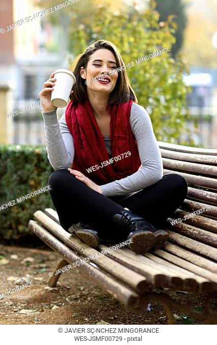 Portrait of smiling young woman relaxing with coffee to go on a bench