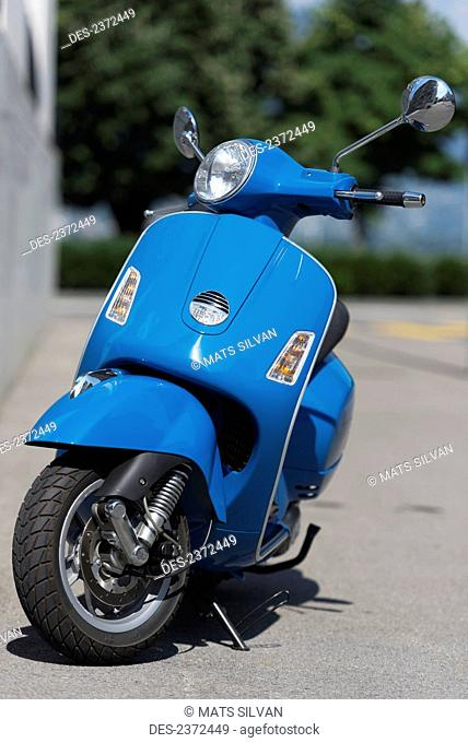 A Blue Motor Scooter Parked On The Side Of A Street; Locarno, Ticino, Switzerland