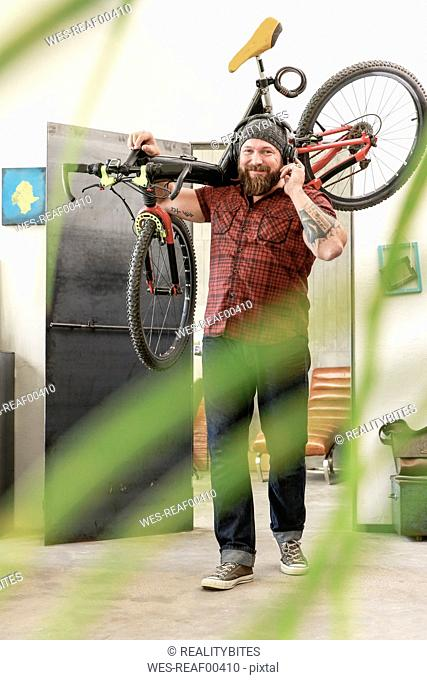 Portrait of smiling man wearing headphones carrying bicycle in office