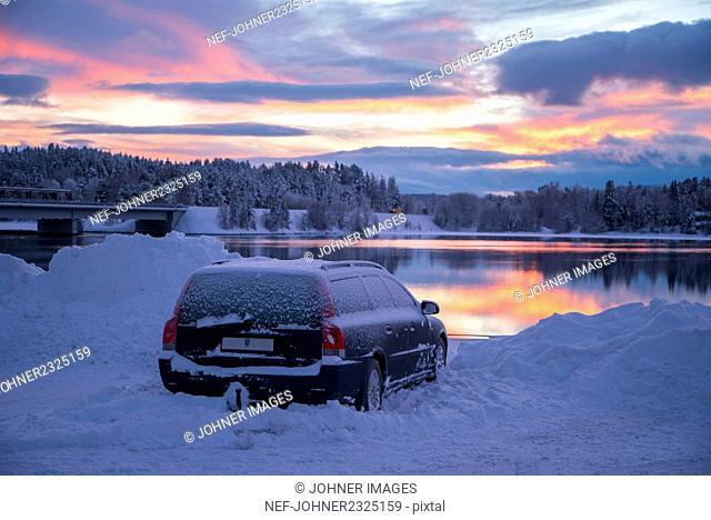 Car by lake at sunset
