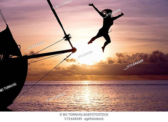 Girl jumping from yacht in sundown. Bora Bora. French Polynesia