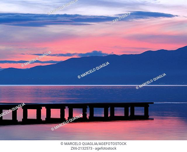 Wooden pier at Trabucador isthmus. Alfacs Bay at dusk. Ebro River Delta Natural Park, Tarragona province, Catalonia, Spain