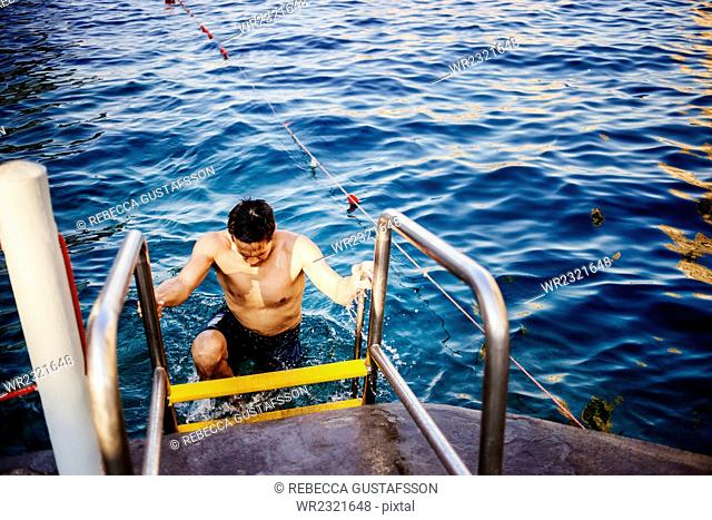 High angle view of wet man climbing ladder at shore