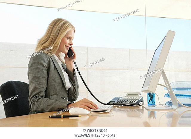 Young woman in office using phone