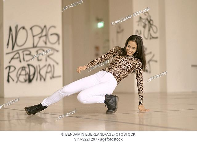 playful woman dancing on floor, wearing fashionable leopard print sweater, in Munich, Germany